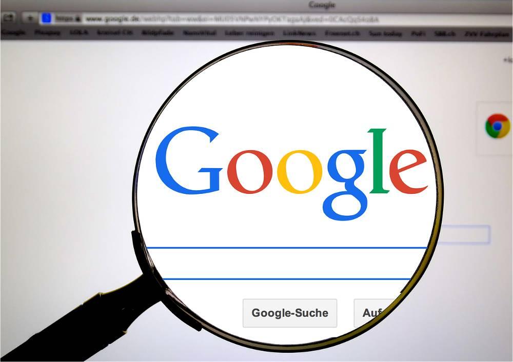 Bild mit Lupe über dem Google-Logo als Synonym für das Thema Google Suchmaschinenoptimierung