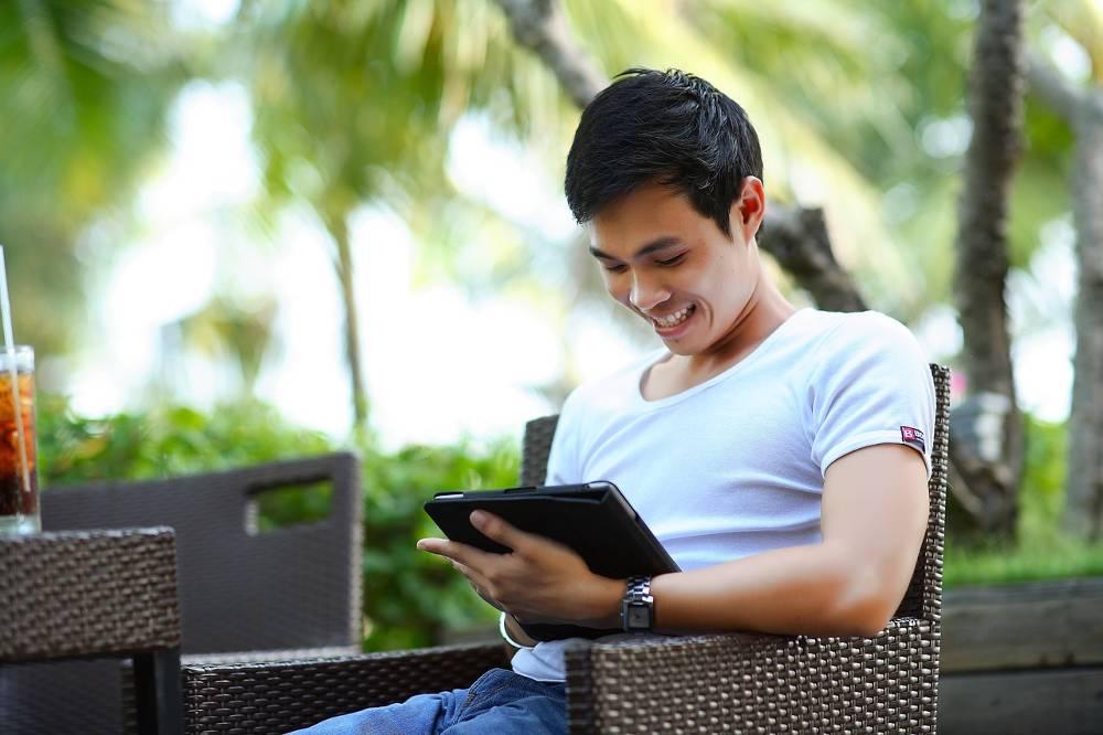 Junger Mann mit Tablet widmet sich Schulungen für SEO Experten