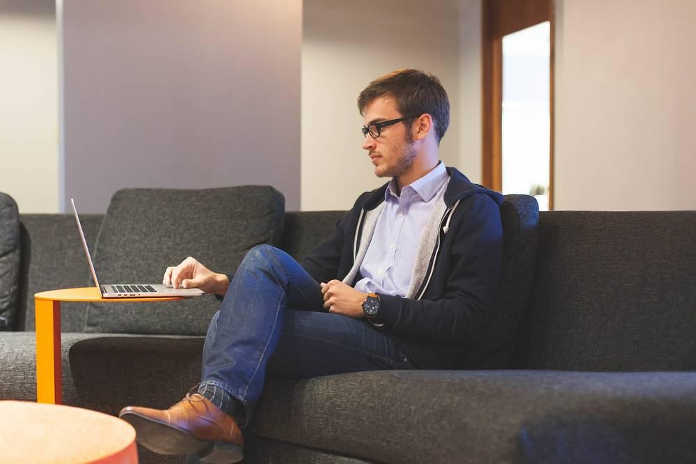 Junger Unternehmer auf der Couch am Computer während er am SEO Workshop online arbeitet